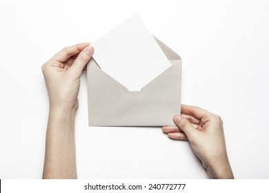A female(woman) hand hold a letter with envelope isolated white at the studio.