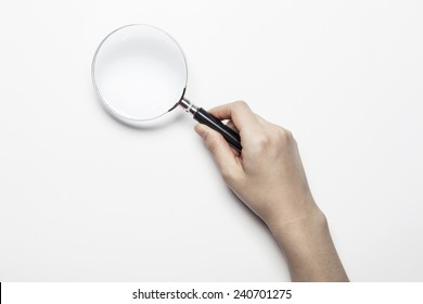 A female(woman) hand hold a magnifier(reading glass) isolated white at the studio.