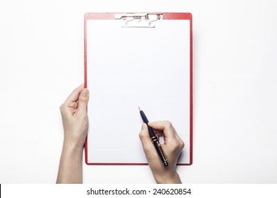 A female(woman) hand hold a pen and red clipboard with paper(document, report) isolated white, top view at the studio.