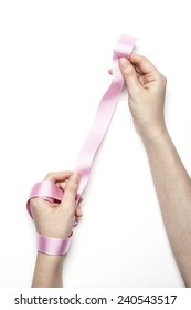A female(woman) hand hold a pink ribbon isolated white background at the studio.