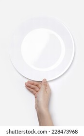 Female(woman) hand hold a white dish(plate) isolated white and top view.