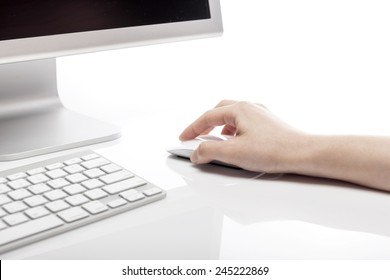 A female(woman) hand hold a white mouse with computer and keyboard isolated white at the studio.