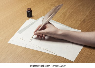 A female(woman) hand hold(write) a feather quill pen with ink on the letter paper and wood desk(table) at the studio.