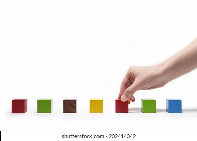 A female(woman) hand pick up(hold) a wood block among many color(red, green, blue, yellow) wood blocks isolated white at the studio.