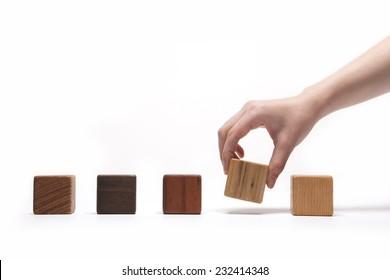 A female(woman) hand pick up(hold) a wood block among many wood blocks(oak, walnut, teak, cherry) isolated white at the studio.