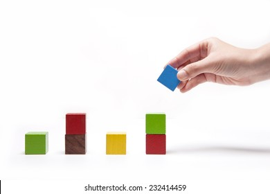 A female(woman) hand pick up(hold) a wood block among Color wood cube blocks(yellow, red, blue, purple) like bar graph symbolizing sales growth isolated white at the studio.