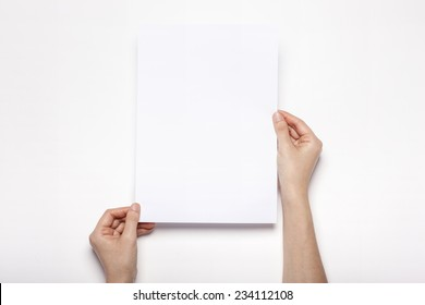 A female(woman) hands hold a empty(blank) white paper(a4) isolated white, top view at the studio.