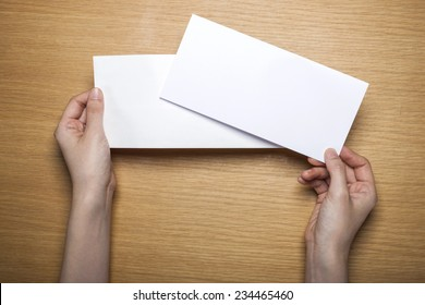 A female(woman) hands hold a empty(blank) white letter and envelope on the desk(table), top view at the studio.