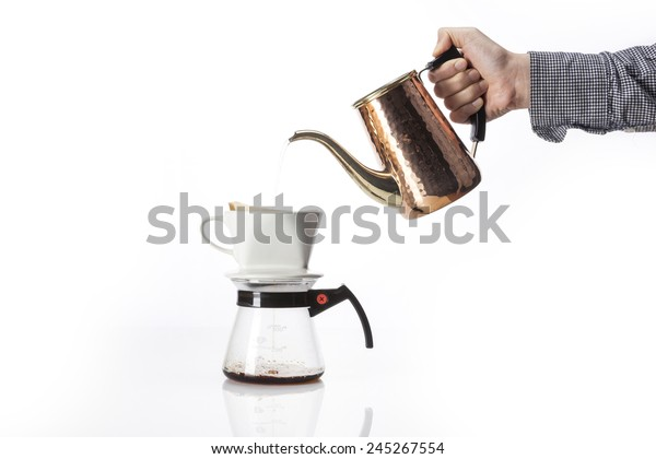 A female(woman) hold a brass coffee pot and drop to the dropper and glass pot for hand- drip coffee isolated white at the studio.