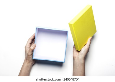 A female(woman) hold(open) a empty(blank) present box(yellow, blue) isolated white at the studio.