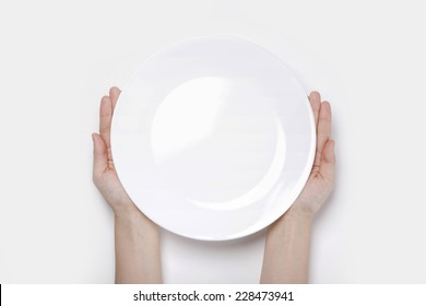 Female(woman) two hands hold a white dish(plate) isolated white and top view.
