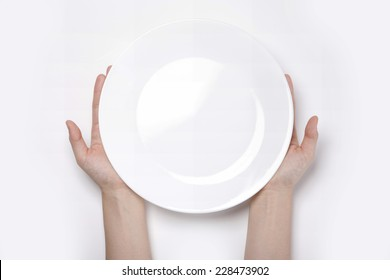 Female(woman) two hands hold(support) a white dish(plate) isolated white and top view.