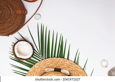 Feminine accessories, greem leaves and half of the coconut. Summer flat lay.