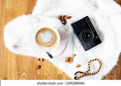 Feminine background  coffee cup and retro camera on white fluffy surface. Blogger, photogapher, travelers lifestyle.