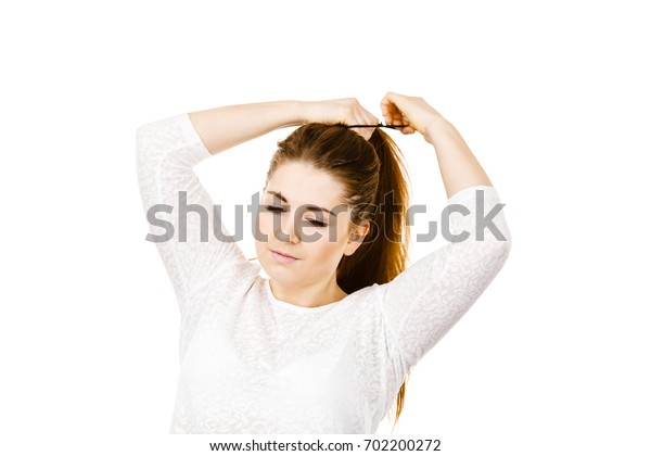 Feminine beauty concept. Portrait of beautiful young woman touching her long brown hair