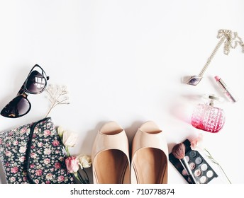 Feminine beauty white background, cosmetics, purse, flowers, sunglasses. Nude shoes,parfume, hair accessory. Top view. Beauty products. Space for text. Fashion background.