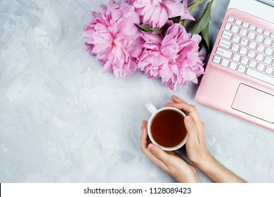 Feminine business mockup with pink laptop, peonies bouquet and woman's hands holding cup of warm tea, flatlay on cement background with copyspace