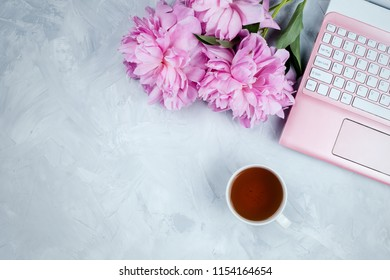 Feminine business mockup with pink laptop, peonies bouquet and cup of warm tea, flatlay on cement background with copyspace
