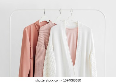 Feminine clothes in pastel pink  color on hanger on white background.  Elegant dress,  jumper, shirt and other fashion outfit. Spring cleaning home wardrobe. Minimal concept.