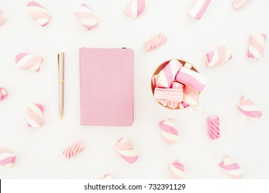 Feminine concept of marshmallow with cappuccino mug and notebook on white background. Flat lay, top view