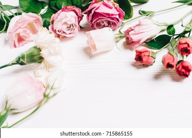 Feminine desk workspace frame with pink roses and petals on white wooden background. Flat lay, top view. Flower background. Women's day, mother's day.