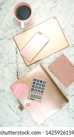 Feminine desk workspace with rose gold accessories on white marble table, flatlay overhead.