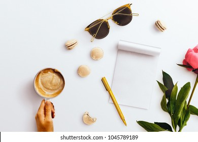 A feminine desktop flatlay hero image, with a coffee cup, notepad, peony flower and gold accessories. Negative space to the left hand side, on a plain white desk background.