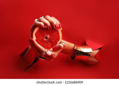 Feminine elegant hands. Female hands with red nails through a hole in a red background are holding a grapefruit fruit.