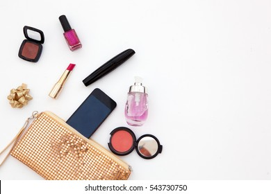 Feminine fashion background. Content of ladies handbag. Red lipstick, brush mascara, eyeshadow palette and nail polish. Flat lay beauty accessories for makeup and open yellow clutch. Top view photo