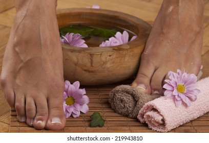 Feminine feet in foot spa bowl with flowers and towels