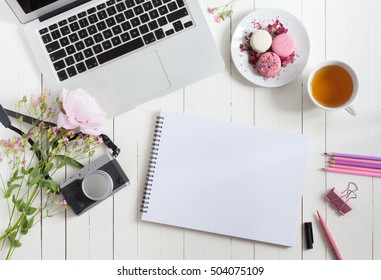 Feminine flat lay workspace with laptop, cup of tea, macarons, photo camera and flowers on white wooden table. Top view mock up.