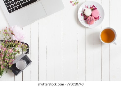 Feminine flat lay workspace with laptop, cup of tea, retro camera, macarons and flowers on white wooden table. Top view mock up. Empty space for your text.