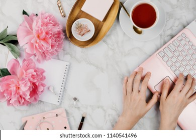 Feminine flatlay mockup with pink peonies, daisies, notebooks, cup of warm tea and female hands printing on laptop on marble table