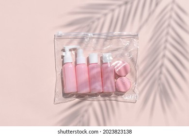 Feminine flatlay with travel size pink cosmetic bottles in bag on neutral pastel background. Palm leaves shadows. Minimalist skin or body care beauty products for vacation or journey. Top view.