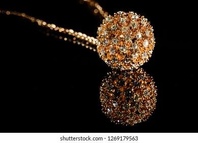 Feminine golden bracelet with shiny gems close up macro on plain black background, fashion accessoires