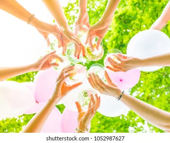 Feminine hands clinking glasses at bachelorette party outdoors