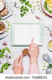 Feminine hands shows with finger on tablet with copy space on white desk background with healthy eating ingredients , top view, frame. Modern cooking , clean diet nutrition or detox food concept