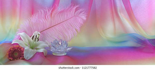 Feminine Holistic Background - pink feather, white lily, glass lotus candle and pink flower head on left with rainbow chiffon behind and copy space to the right, ideal for a website banner