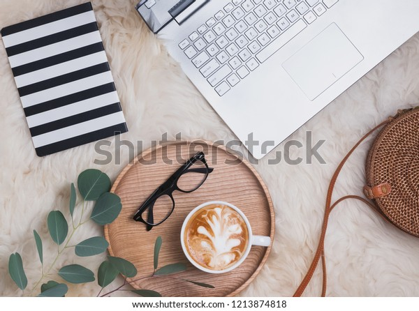 Feminine home workplace concept. Laptop, coffee, glassses and other accessories, top view