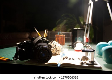 The feminine lifestyle of a Mexican photographer who uses camera, thread, makeup, nail stamp, cutting blade, cutting board, perfume and lipstick, weights, swimming goggles.