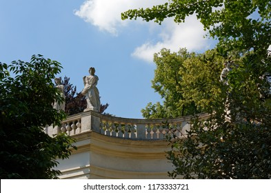Feminine marble statues on a neoclassic balcony in a park
