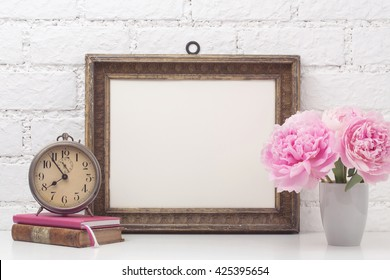 feminine mock-up with vintage photo frame, pink flowers, books and an old alarm clock on a desk