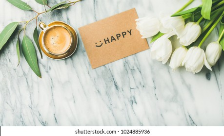Feminine morning layout. Flat-lay of white tulip flowers, cup of coffee and card with word HAPPY over light marble background, top view, copy space.