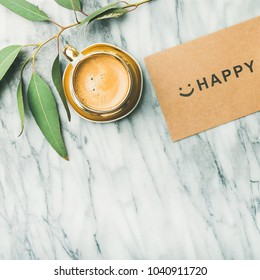 Feminine morning layout. Flat-lay of white tulip flowers, cup of coffee and card with word HAPPY over light marble background, top view, copy space, square crop.