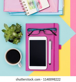 Feminine Office Desk Working Space Flat Lay. Top view photo of workspace with smartphone, coffee, notepad and woman fashion magazines.