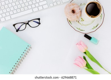 feminine office supplies with turquoise notebook, tulips, coffee and donuts.Flat lay.Top viw