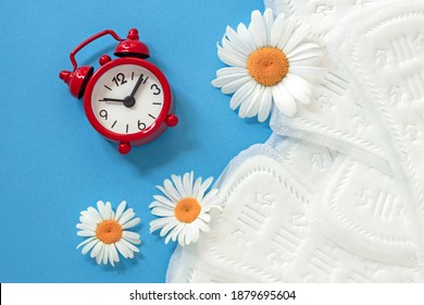 feminine sanitary pads, white chamomile flowers, alarm clock on blue background, concept of feminine health and hygiene, menopause, periodic menstruation