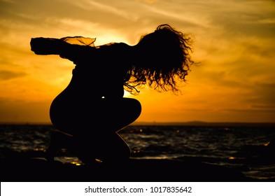 feminine silhouette on sunset background