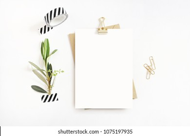 Feminine stationery,  desktop mock-up scene. Blank greeting card, craft envelope, washi tape and golden paper, binder clips with olive branch.White table background. Flat lay, top view.