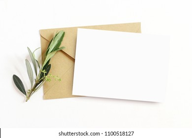 Feminine stationery,  desktop mock-up scene. Blank greeting card and craft envelope with olive branch.White table background. Flat lay, top view.